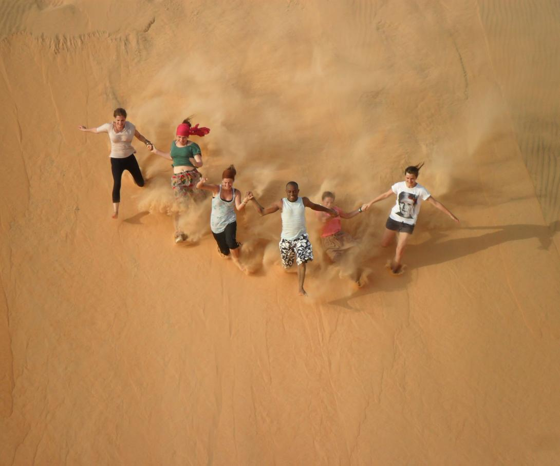 Projects Abroad volunteers run down a sand dune as part of their gap year activities in Senegal.